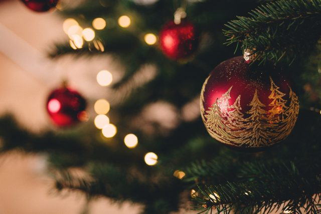 Photo of Christmas tree decorated for the holidays. Adorned with round red ornaments and white strings of lights. A closeup of one ornament shows a glittery tree setting with festive gold trim.